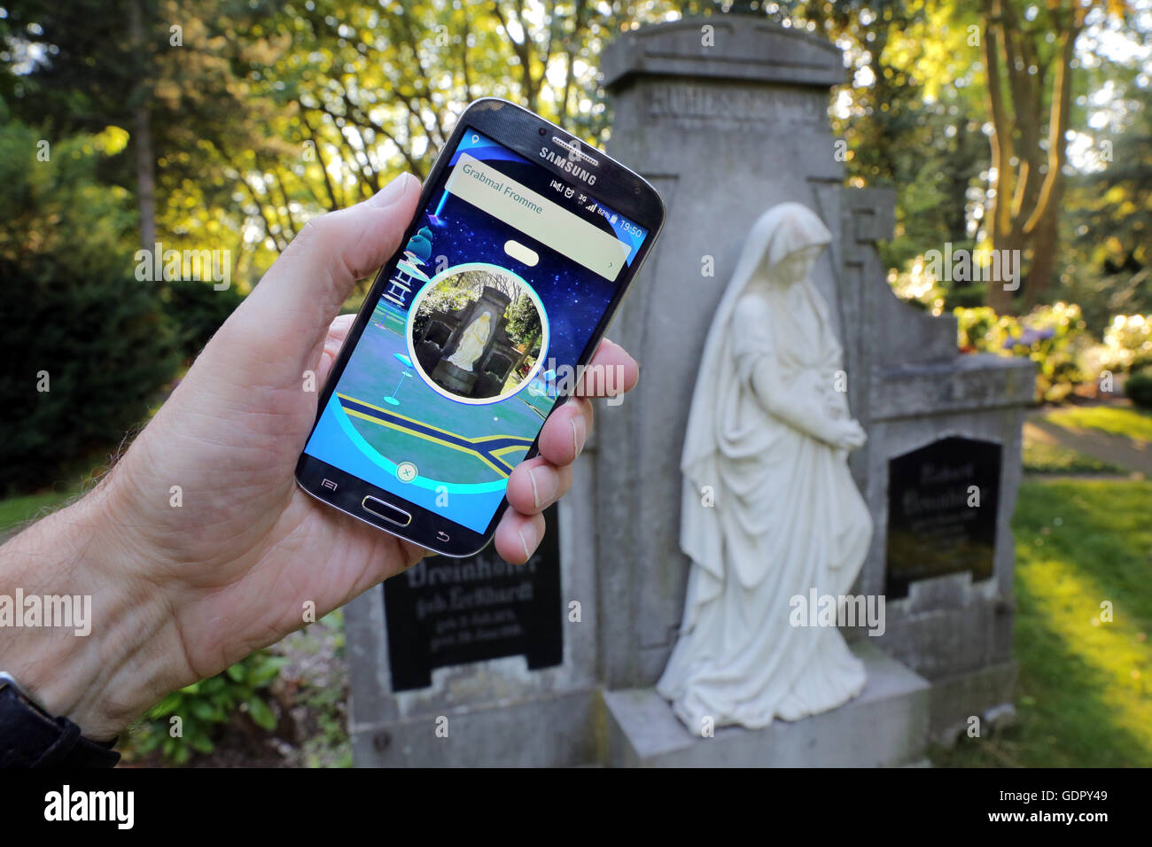 Pokémon go-player with his cellphone on a cemetery in Dortmund, Germany Stock Photo