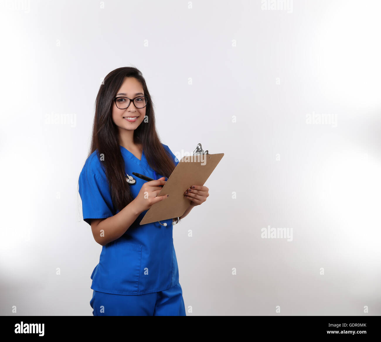 A young hispanic nurse in blue scrubs wearing glasses. Stock Photo