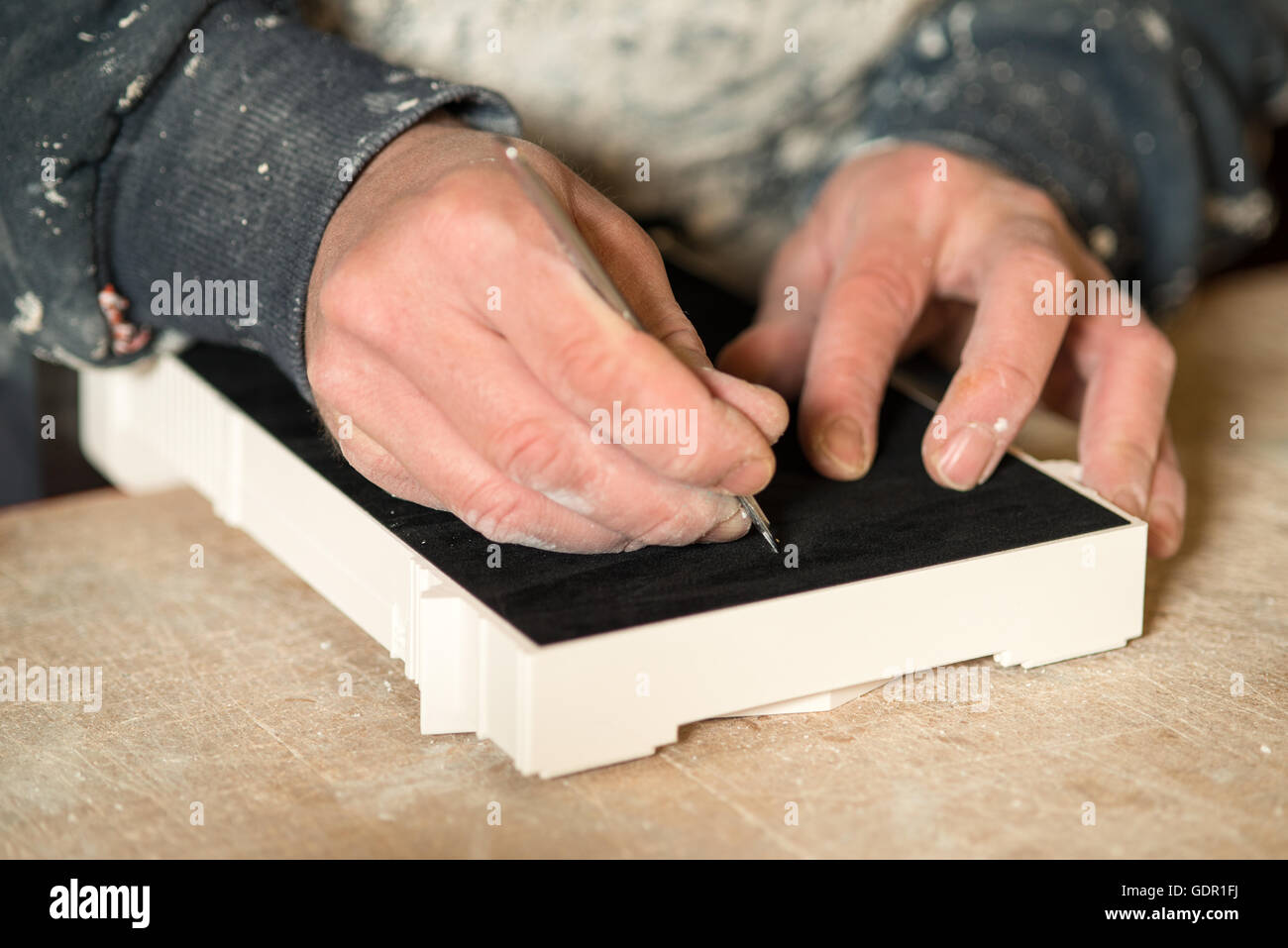 A hand with a precision knife cutting a portion of black felt paper on a plater model - Stock Image