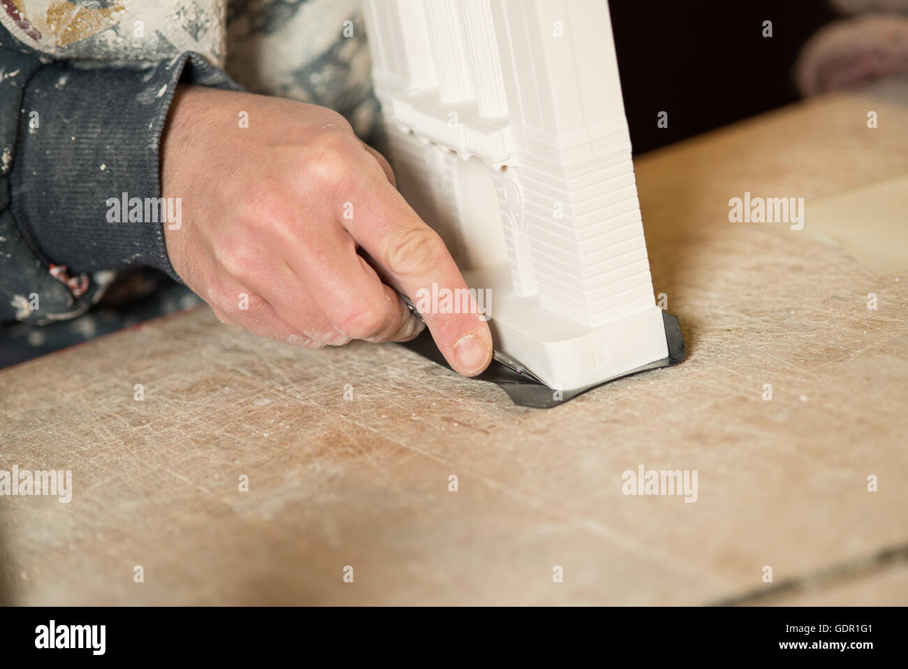 Hand trimming black paper under the base of a plaster model building using a precision blade on a wooden table - Stock Image