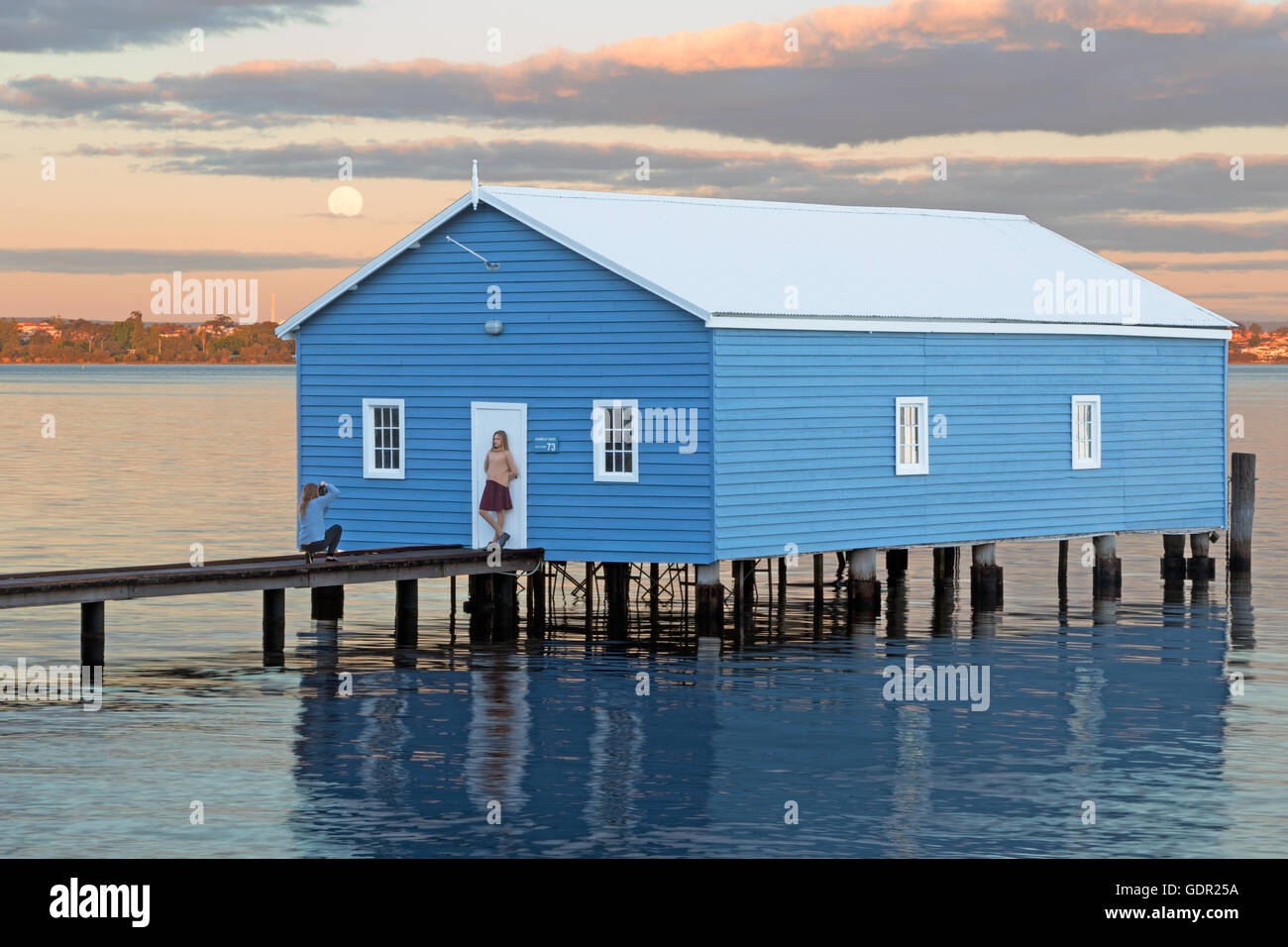 An unidentified photographer and model captured as the moon rises at  Crawley Edge Boatshed in Perth, Western Australia. - Stock Image
