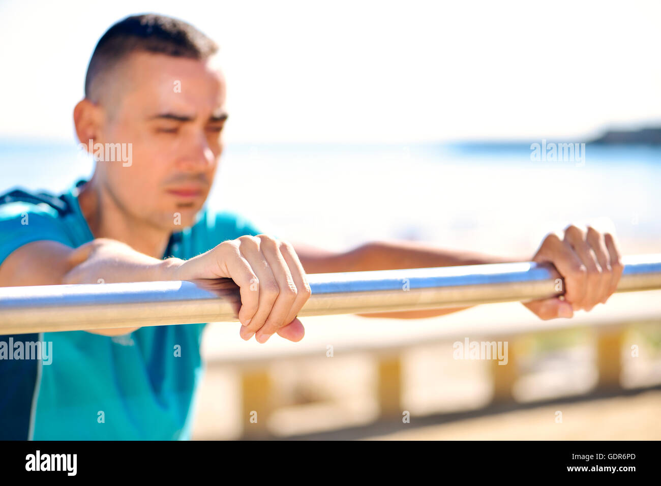 closeup of a young caucasian sportsman wearing sport clothes doing incline push-ups outdoors next to the sea - Stock Image