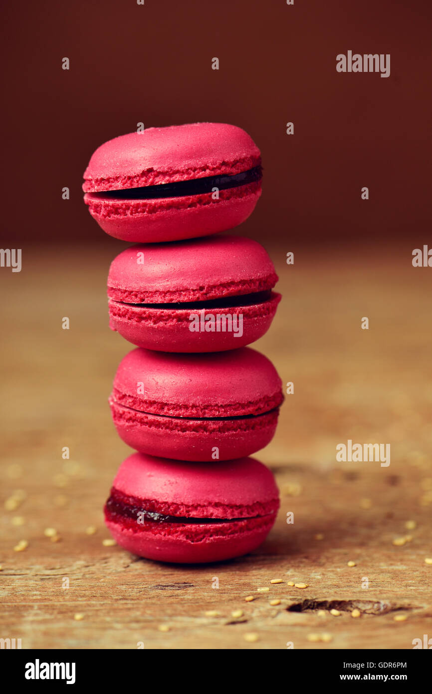 a stack of appetizing red macarons on a rustic wooden surface - Stock Image