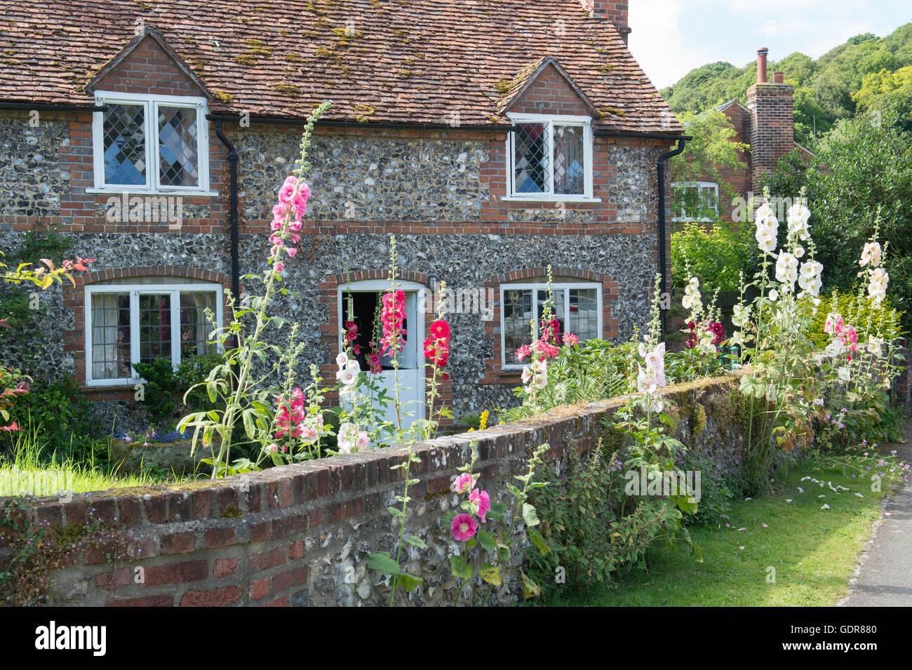 Cottage and hollyhocks, Hambleden, Buckinghamshire, England Stock Photo