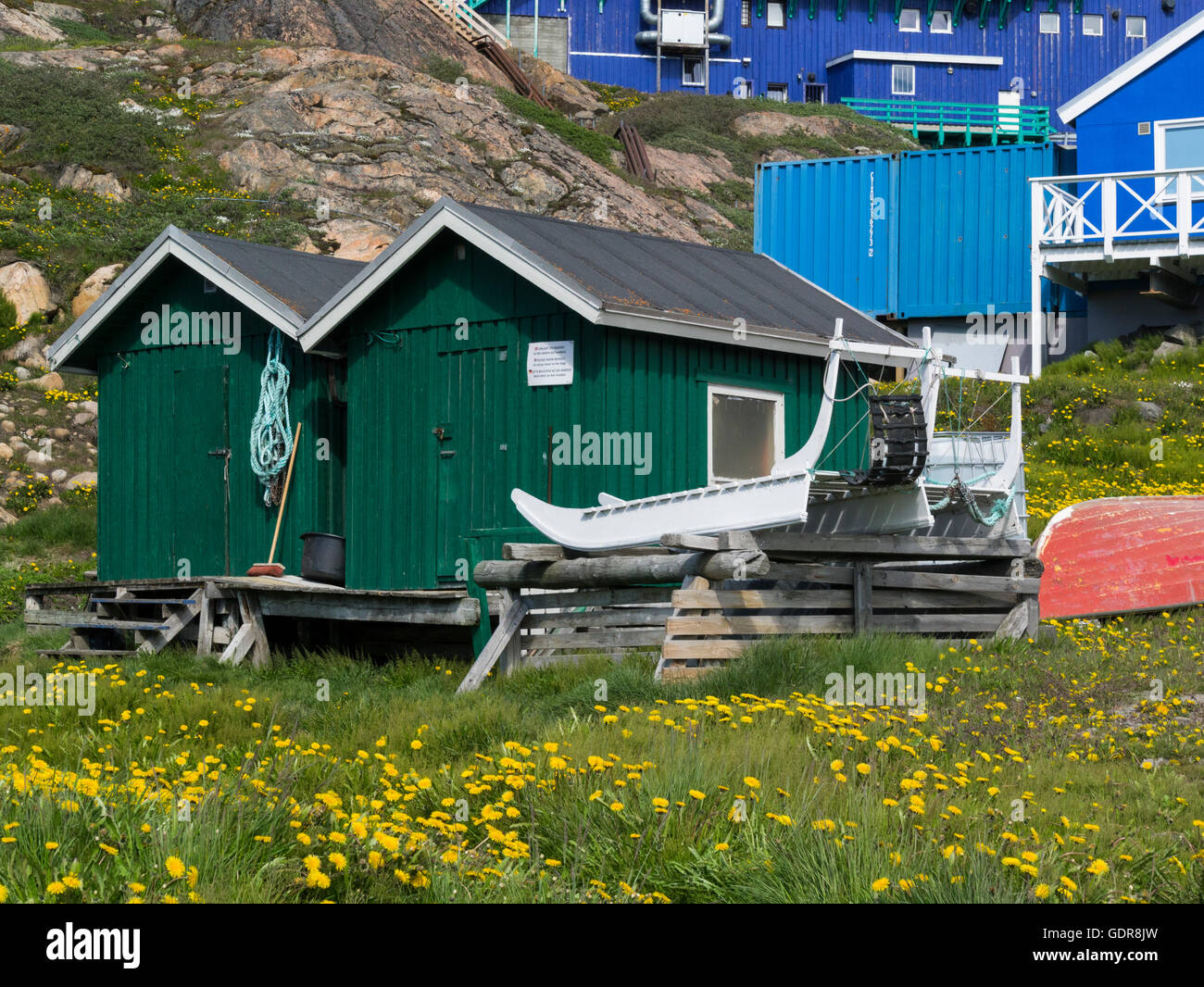 Fishing huts with wooden dog sleds Sisimiut West Greenland second largest city in Greenland Inuit fishing community Stock Photo