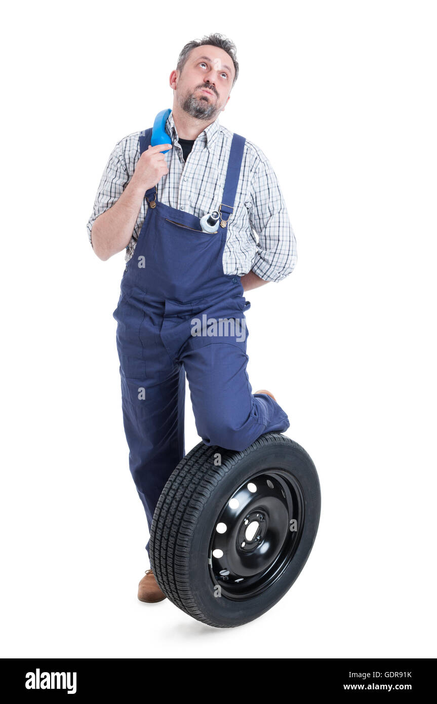 Full body of bored mechanic standing near wheel and holding blue receiver on shoulder isolated on white background - Stock Image
