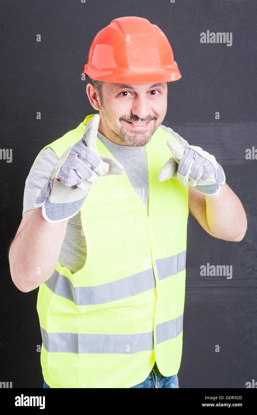 You are the man concept with handsome constructor pointing fingers at you against black background - Stock Image