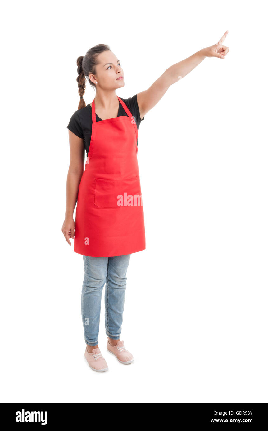 Supermarket young employee with long red apron showing or indicating something isolated on white - Stock Image