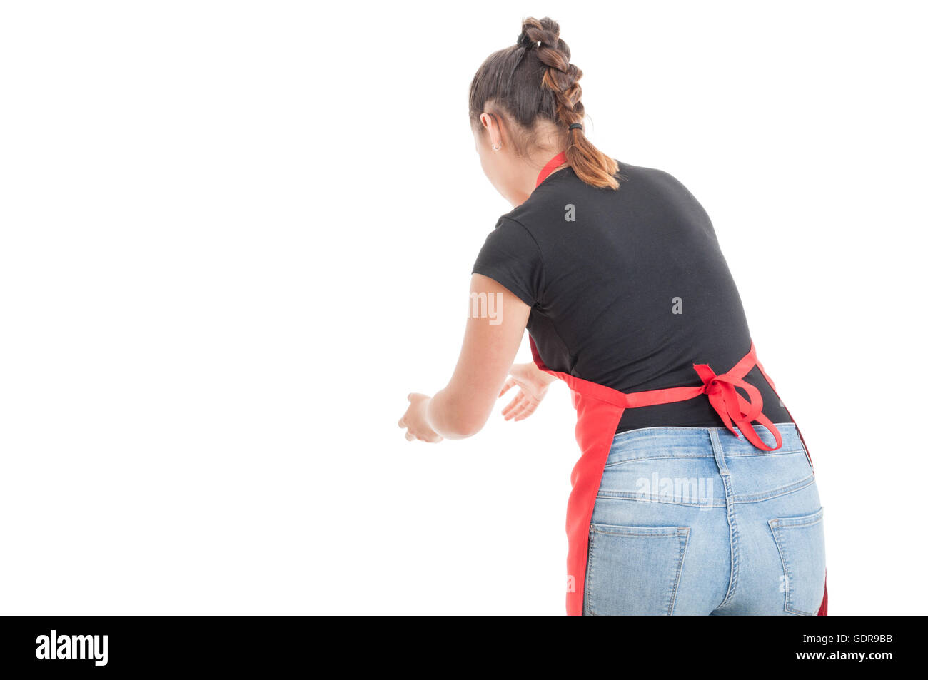 Female employee with apron catching something in back view with copyspace isolated on white - Stock Image