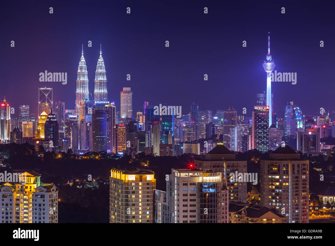 Kuala Lumpur city skyline vibrantly lit at dusk, viewed from west - Stock Image