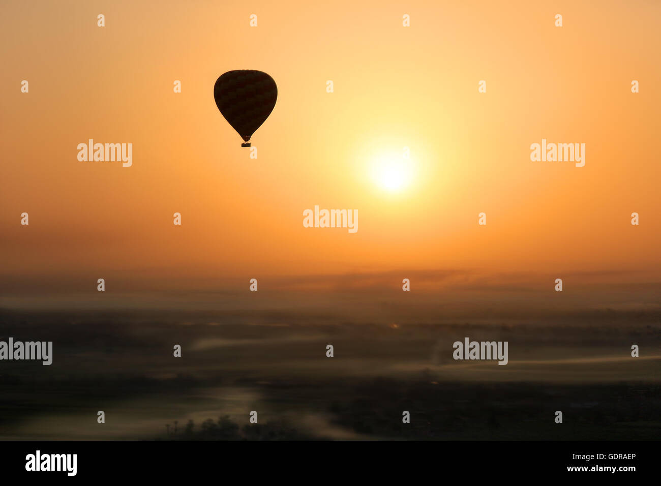 Hot air balloon silhouetted in the  early morning sun during  flight, with foggy patches in the Valley of the Kings, - Stock Image