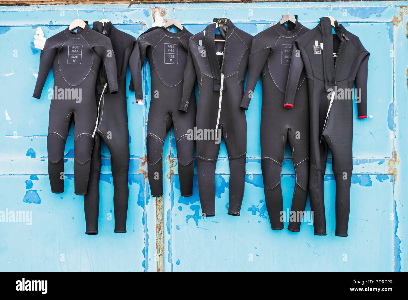 Wet suits drying against a distressed blue and rusted door. - Stock Image