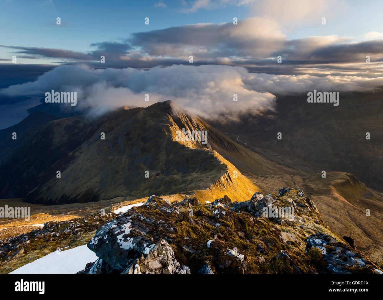 Clouds coming in over the summit of a sidelit Sgur nan Saighead at sunrise - Stock Image