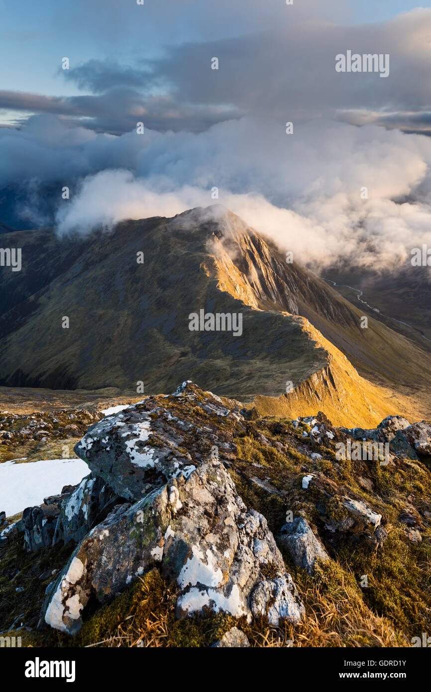 Clouds coming in over the summit of a sidelit Sgur nan Saighead at sunrise Stock Photo