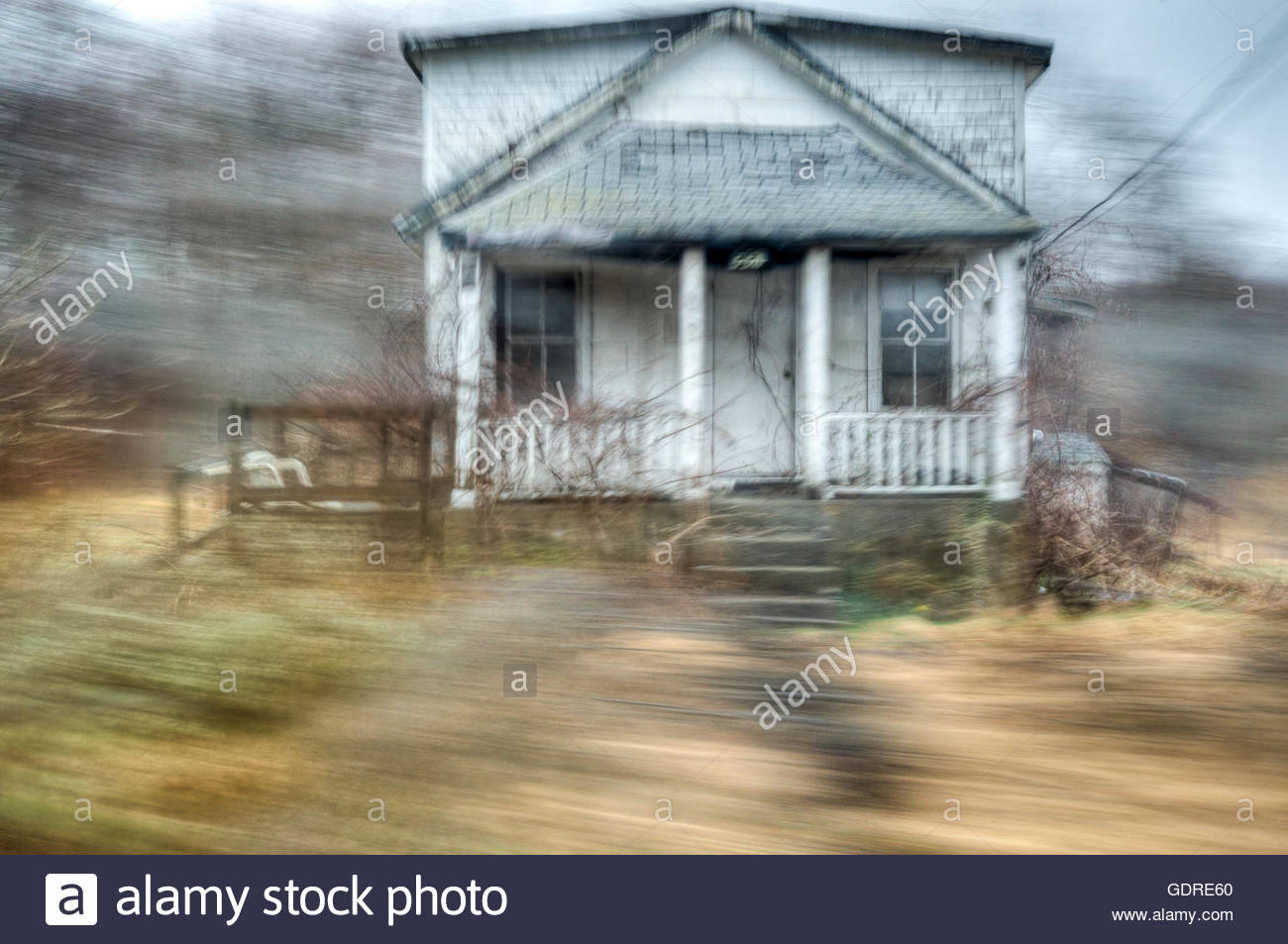 Motion blur speeding by abandoned house - Stock Image