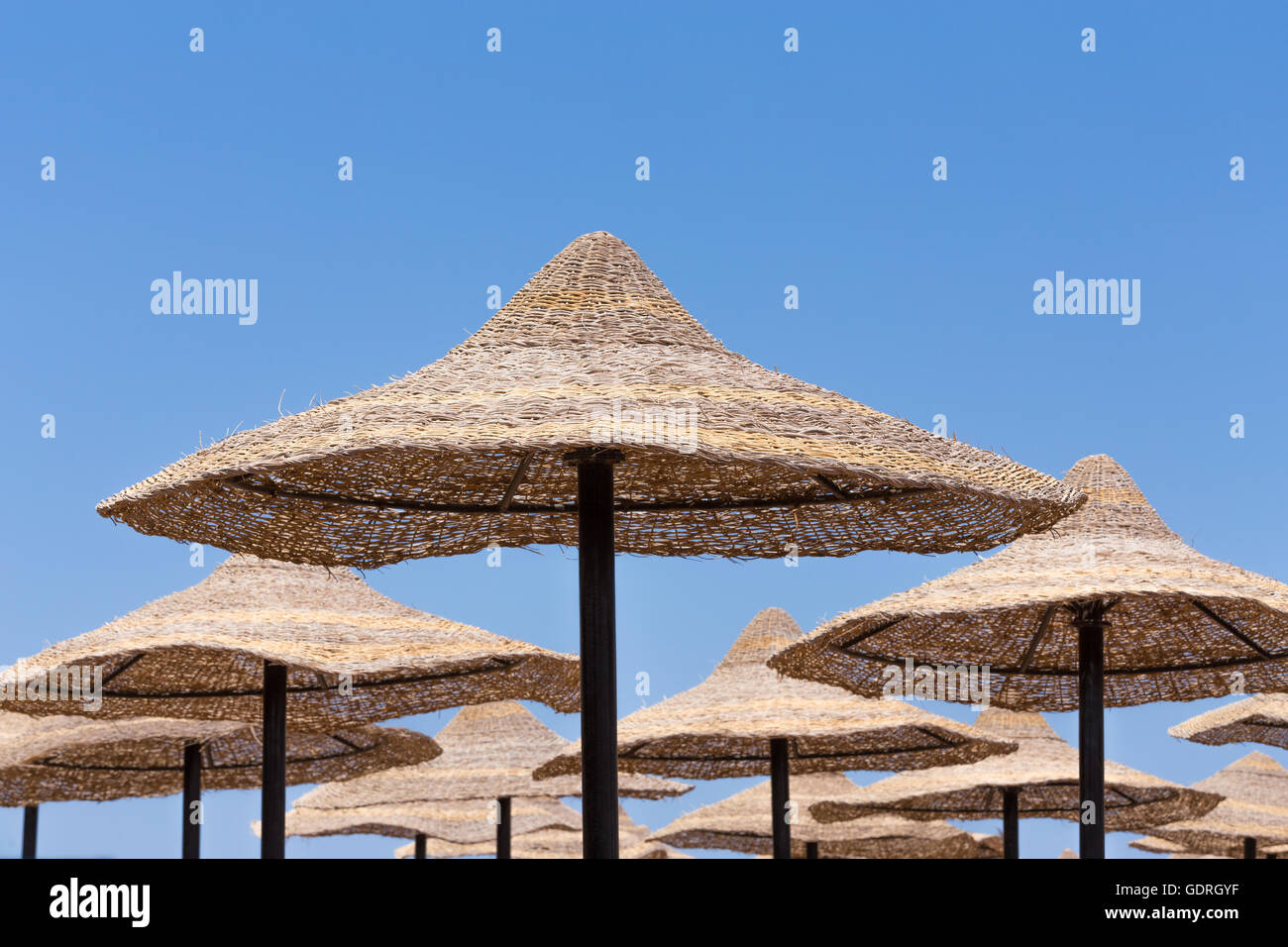Beach umbrellas and blue sky background in egypt paradise beach. holiday vacation summer acation concept. No People. - Stock Image