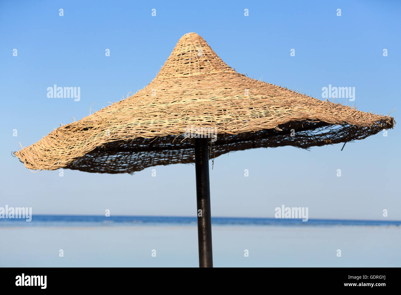 Beach umbrella and blue sky background in egypt paradise beach. vholiday summer acation concept. No People. - Stock Image