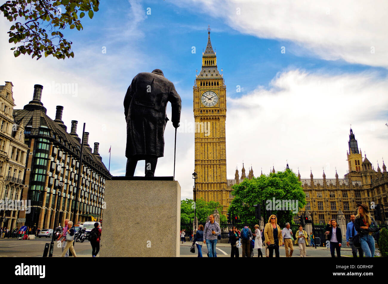 The statue of Sir Winston Churchill gazes upon the majestic Big Ben, a popular tourist spot, in London. - Stock Image