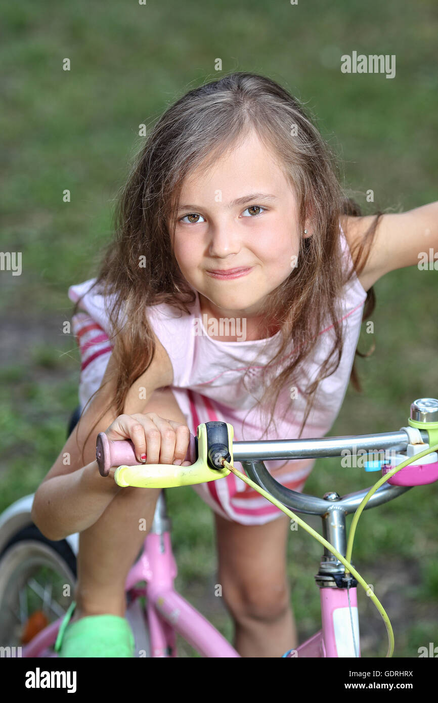 charming and young girl on a bicycle - Stock Image