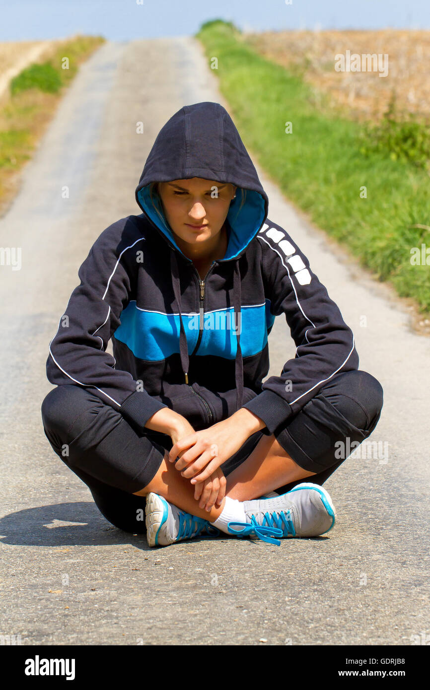 Unhappy young woman sitting on a way - Stock Image