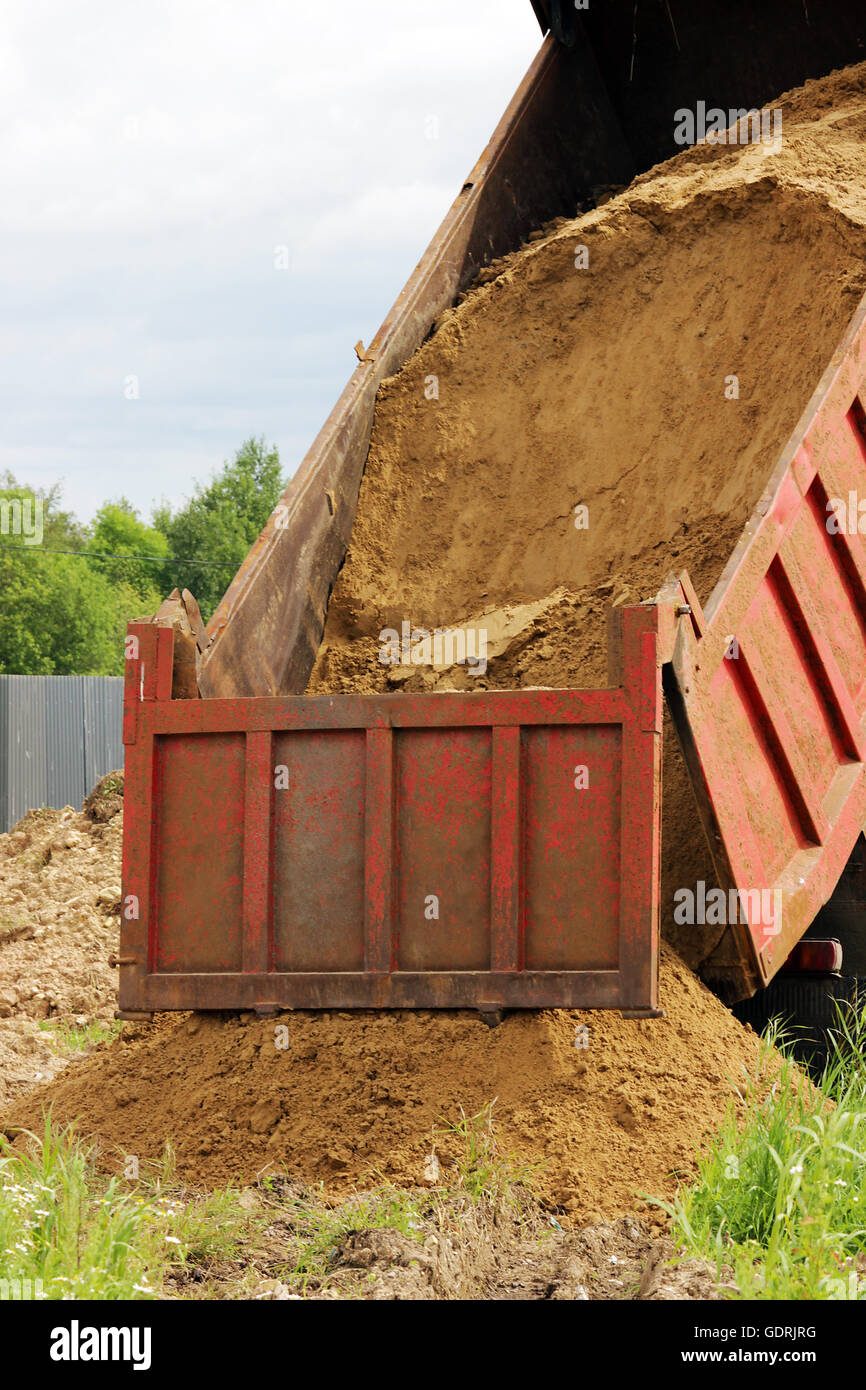 truck unloads sand for backfilling trenches with the pipeline after the accident. - Stock Image