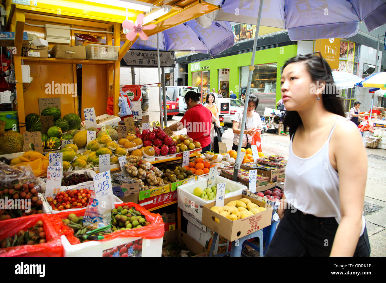 A woman pass by a Hong Kong street market in Kowloon - Stock Image