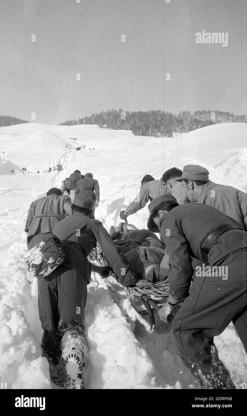 Rescue team carrying a person salvaged after the avalanches at Blons, 1954 - Stock Image