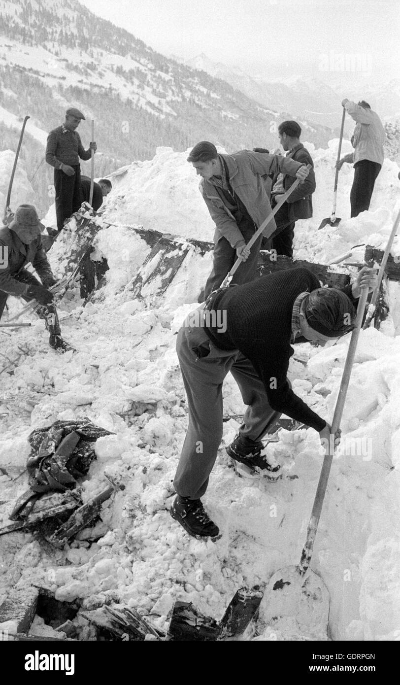 After an avalanche rescuers dig their way through the snow to a building, 1954 - Stock Image