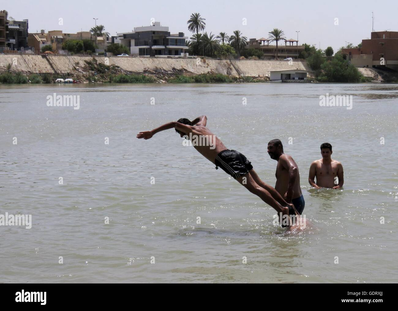 Baghdad, Iraq. 20th July, 2016. An Iraqi man jumps into Tigris river to cool down while temperature reaches above Stock Photo