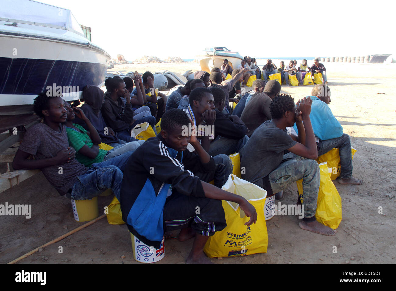 Tripoli. 21st July, 2016. Illegal migrants sit on the dock of Tripoli port in Tripoli, Libya on July 21, 2016. Some - Stock Image