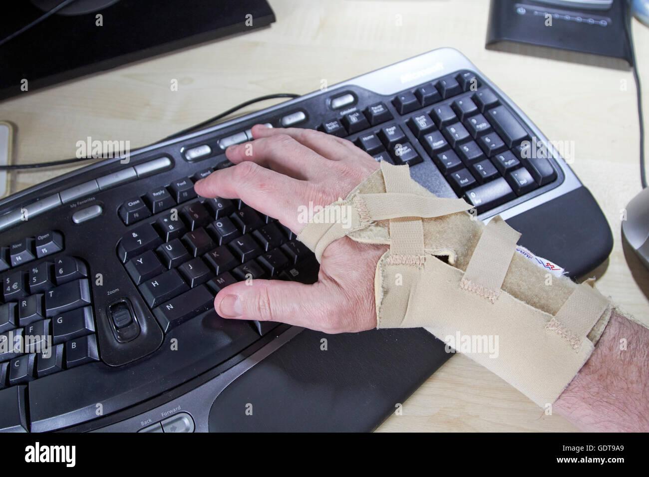 man wearing wrist split due to carpal tunnel syndrome using an ergonomic keyboard - Stock Image
