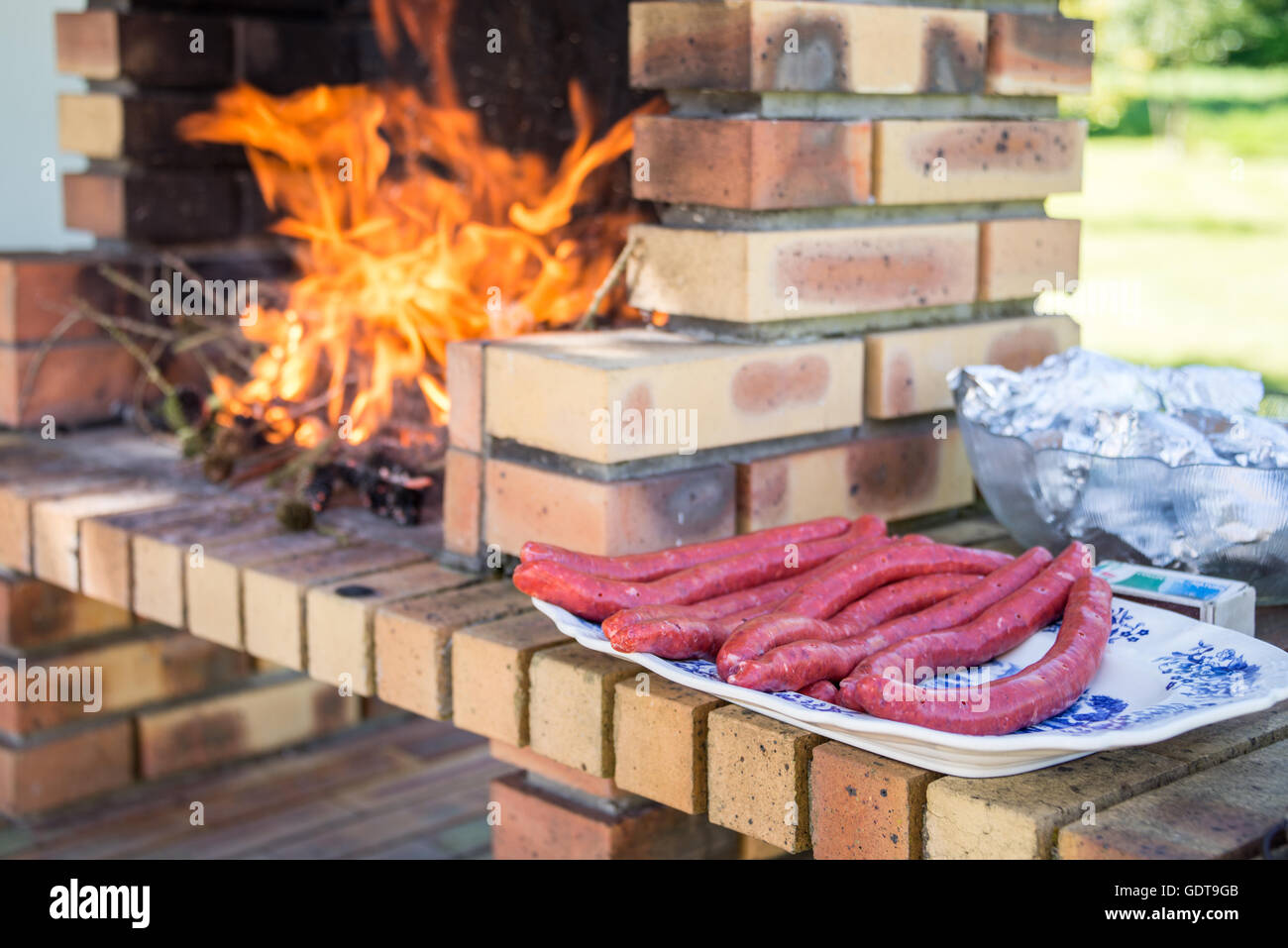 Merguez sausages on a plate, masonry barbecue with fire and flames - Stock Image