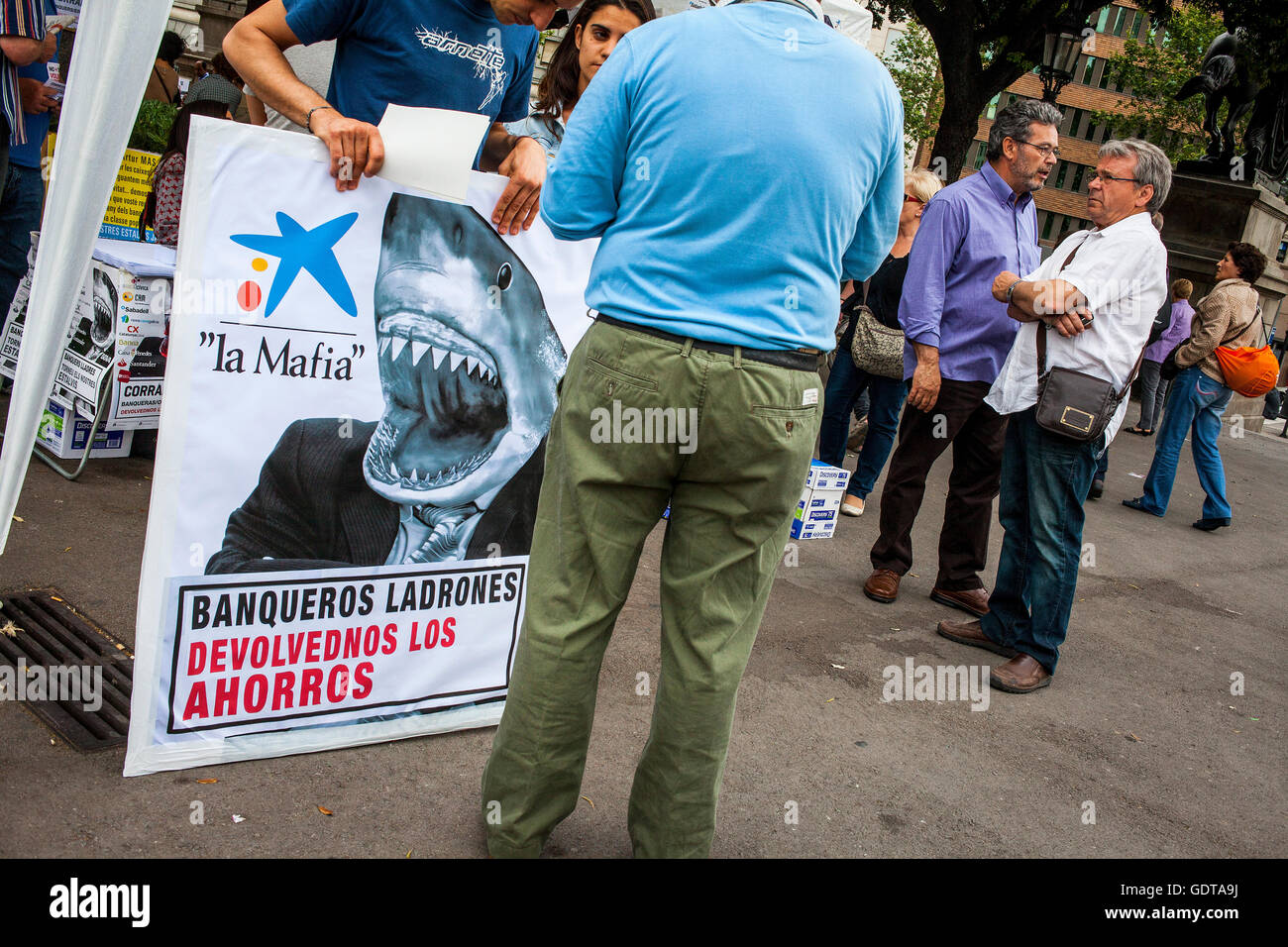 Protester with banner against toxic products of banks.Protests against the depressing social situation.Spanish Revolution - Stock Image