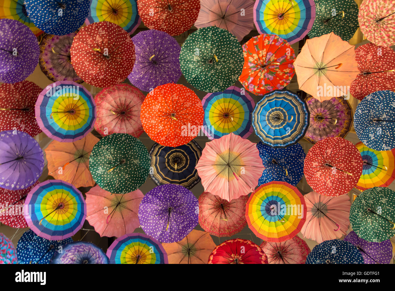 Directly Below Full Frame View of Large Group of Colorful Umbrellas Hanging - Stock Image