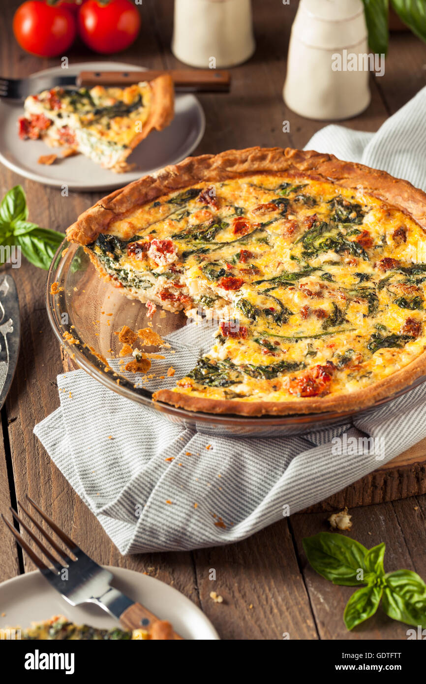 Homemade Cheesy Egg Quiche for Brunch with Spinach and Tomato - Stock Image