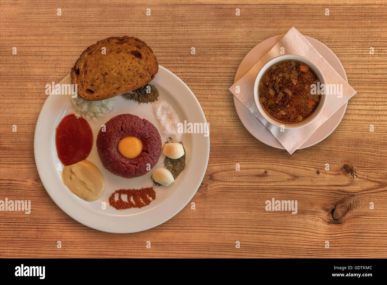 Flat lay of raw beef . Tasty Steak tartare. Classic steak tartare on rustic wooden table with a beef broth. Ingredients: Stock Photo