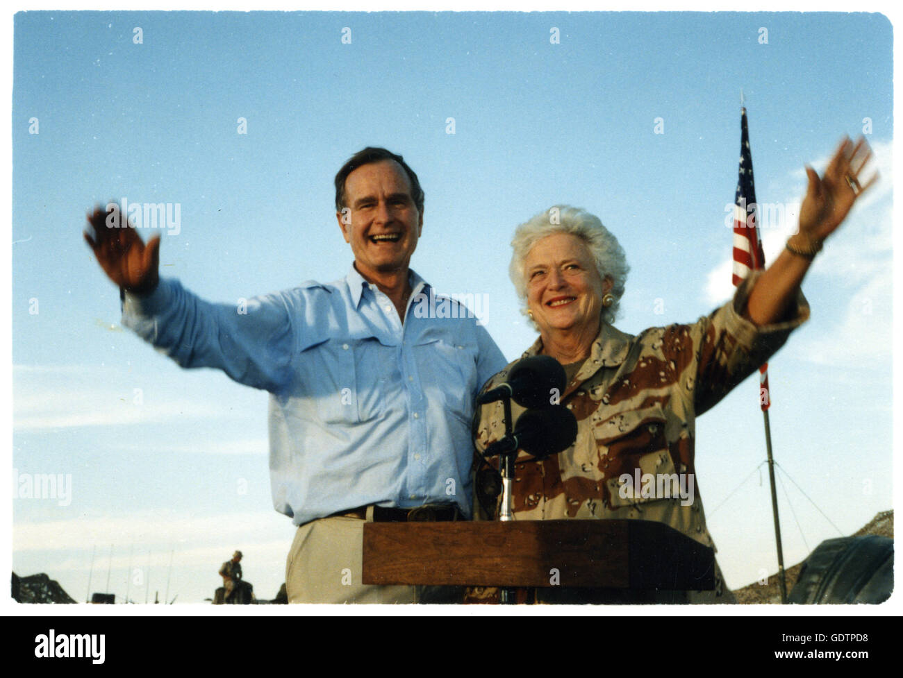 President George Bush and First Lady Barbara Bush wave as they stand in the back of a vehicle during a visit to Stock Photo