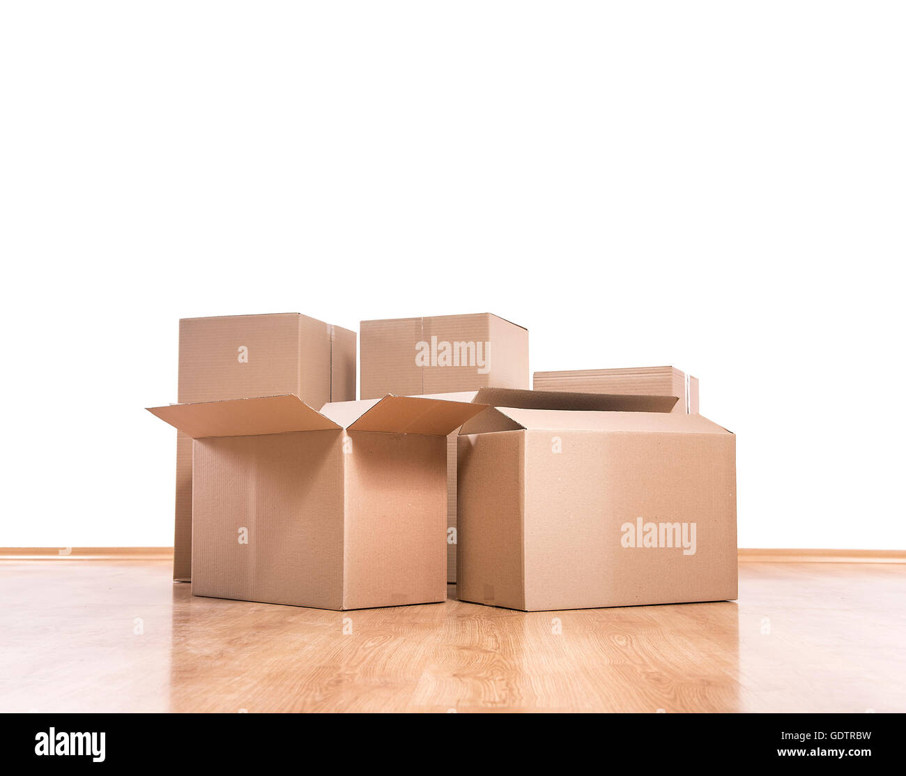 Empty room with a white wall and moving boxes on the floor. Stock Photo