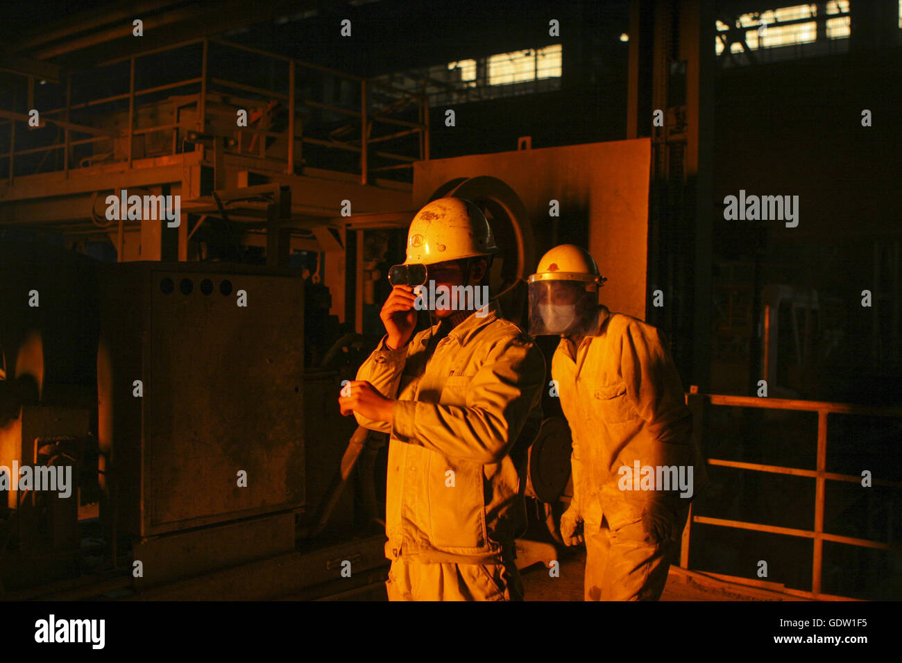 Two technicians observe a furnace during the steel production in Shanghai Meishan Iron und Steel Co - Stock Image
