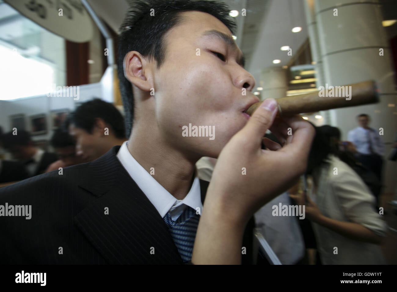 A man try out a cigar at a trade fair - Stock Image