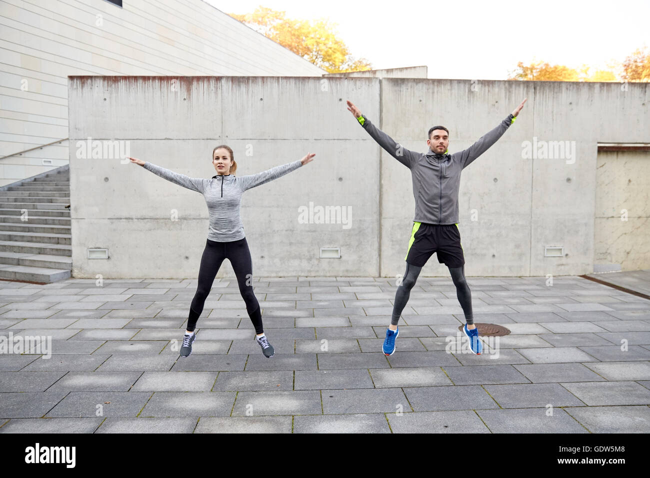 happy man and woman jumping outdoors - Stock Image