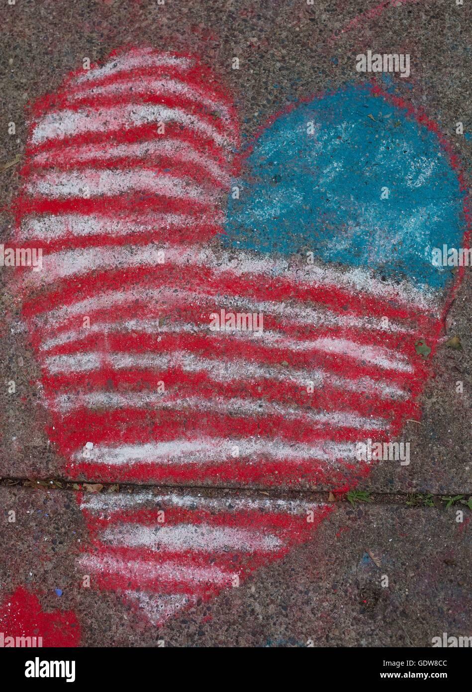 A sidewalk chalk drawing of an American flag inside a heart. - Stock Image