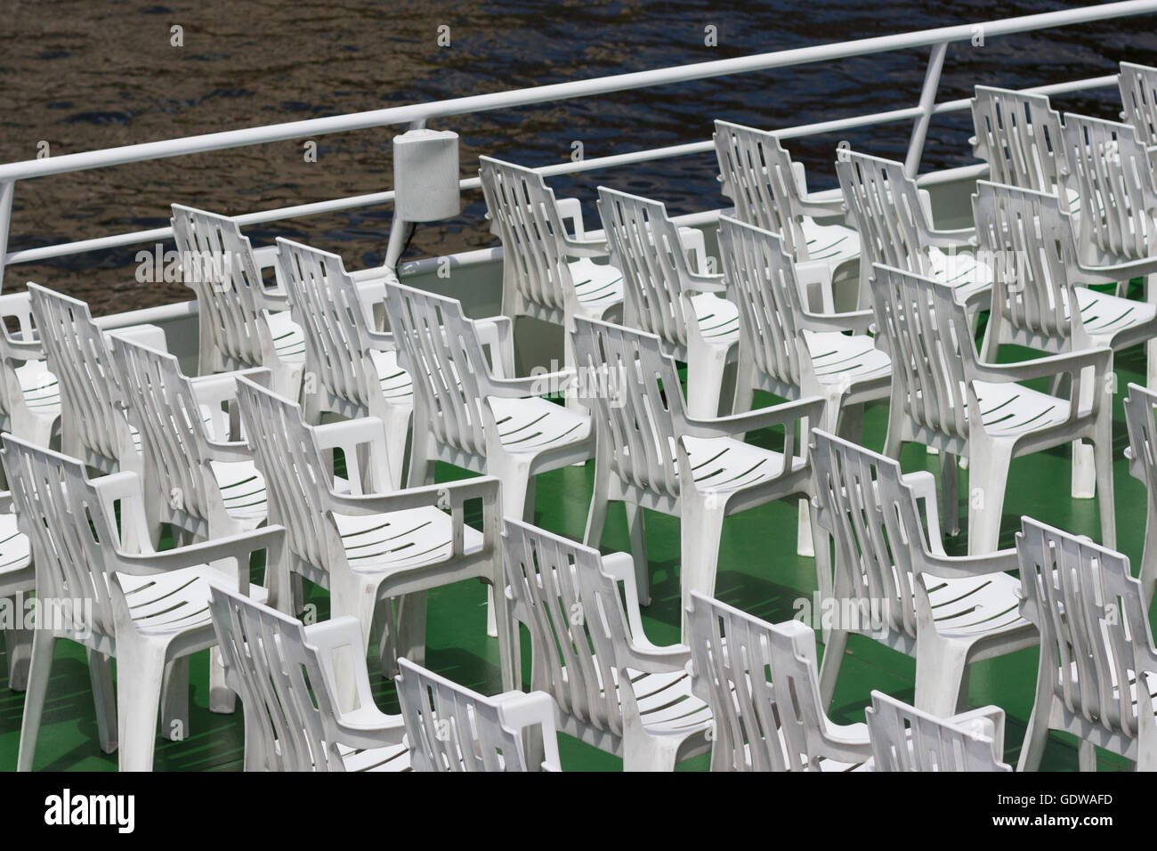 many white empty plastic chairs in rows - Stock Image