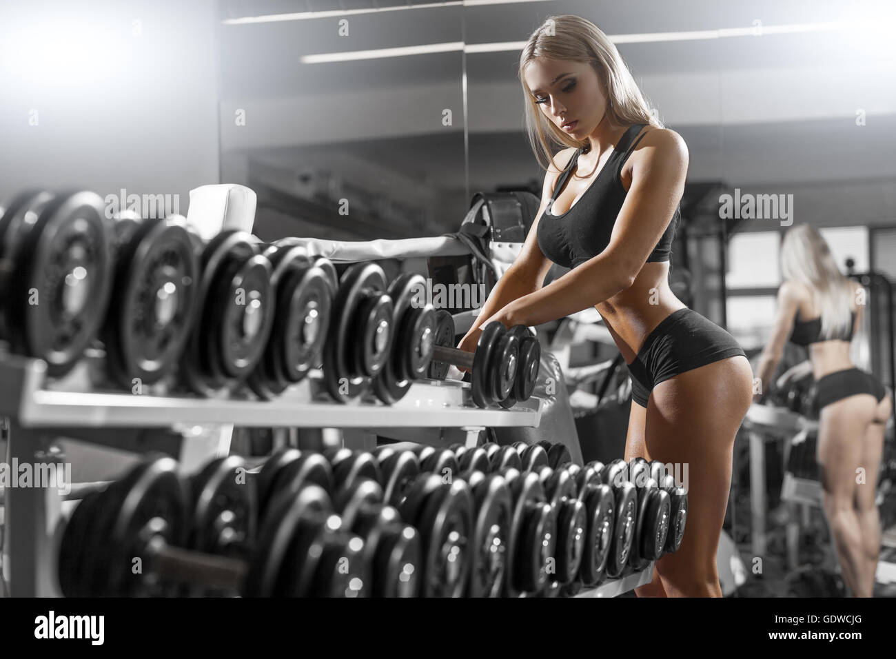 athletic young blondy doing exercise in the gym - Stock Image