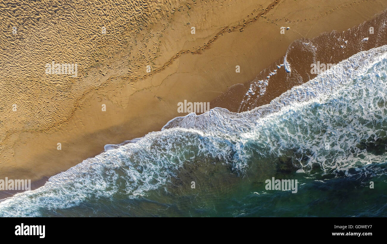 Aerial image of sea waves crashing on a lonely beach in a late summer afternoon. - Stock Image