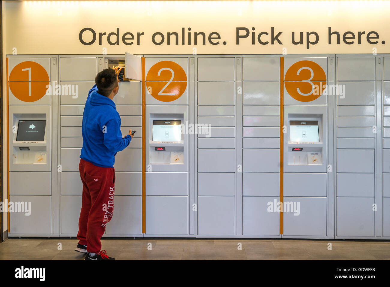 Man reaching into an ecommerce locker while holding his smarthpone as he picks up a package he ordered online - Stock Image
