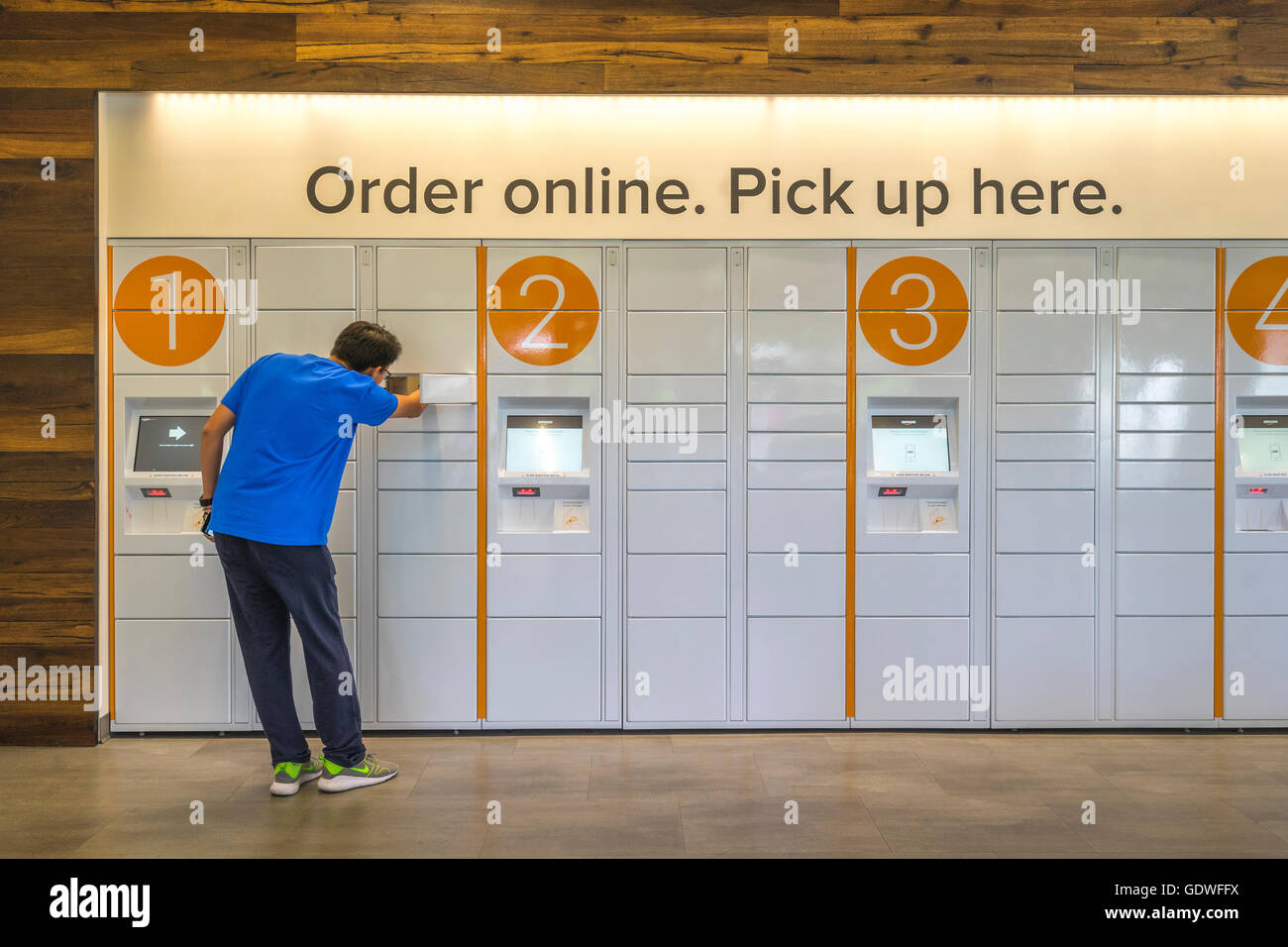 Man reaching into an ecommerce locker to get a package he ordered online - Stock Image