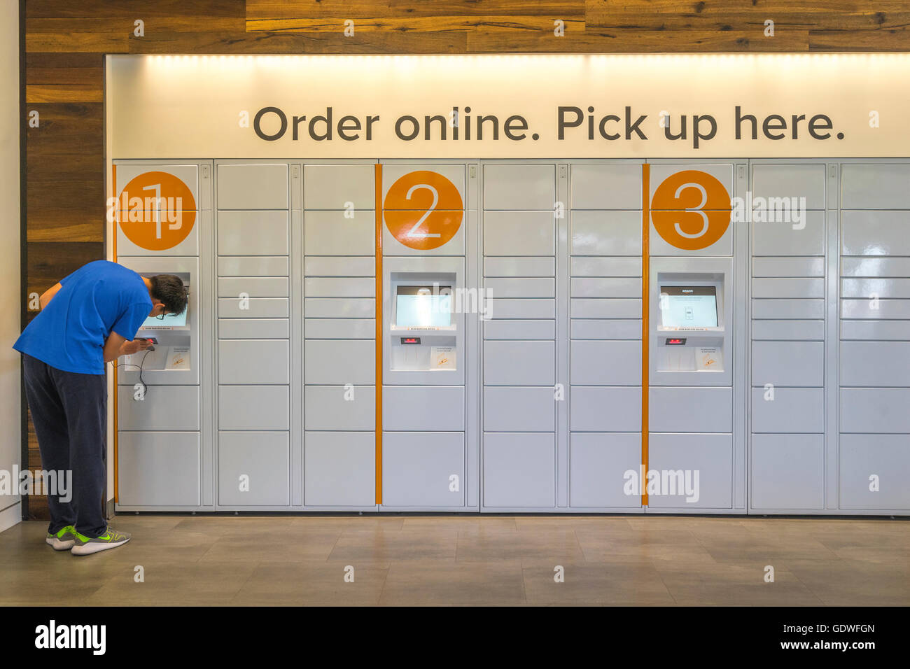 Man scanning his smartphone at an ecommerce locker to get a package he ordered online - Stock Image