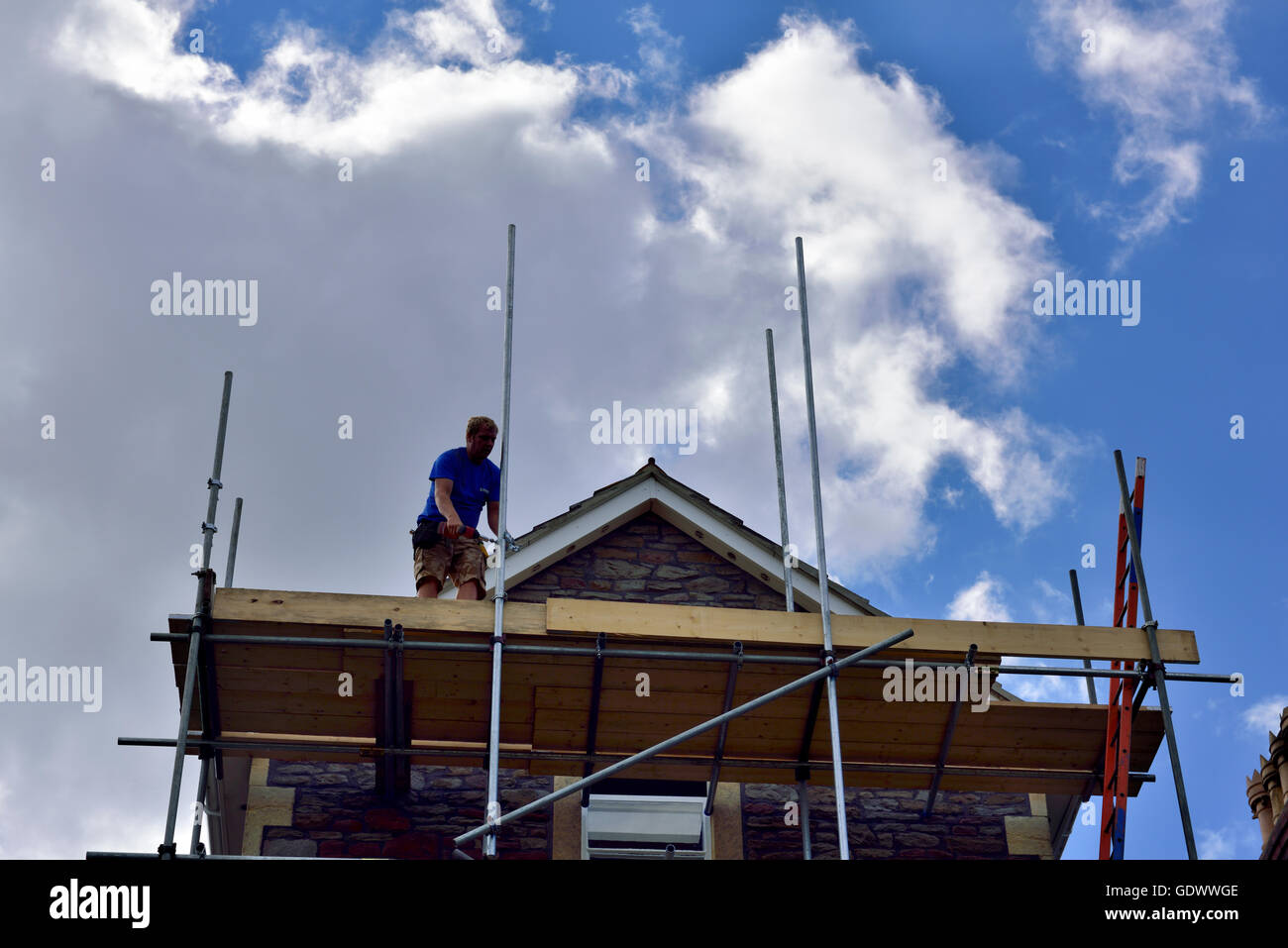 Roof gable apex with scaffolding and scaffolder in silhouette, UK - Stock Image