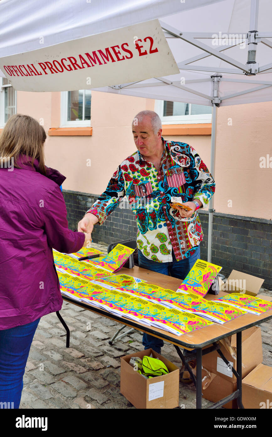 Man at table selling Official Programmes £2 - Stock Image